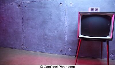 old-fashioned TV with hours on it about block wall in dark...