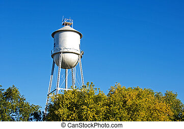 Old-fashioned water tower above trees.