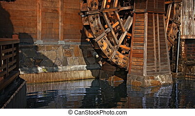 Old fashioned water wheel stands over pond at Chi Lin...