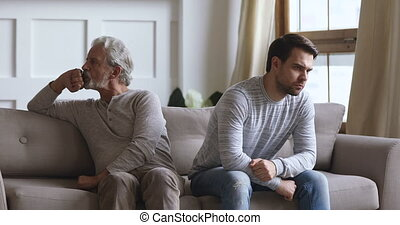 Angry frustrated stubborn senior old father and young adult grown son sit on sofa turn back ignore each other think of family conflict, two age generation gaps and problem in bad relationship concept