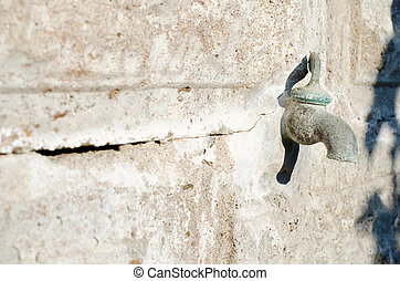 Old faucet protruding from the concrete wall