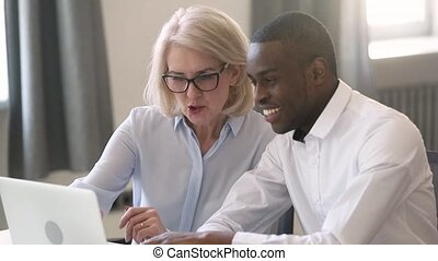 Old female manager teach young african intern explain...