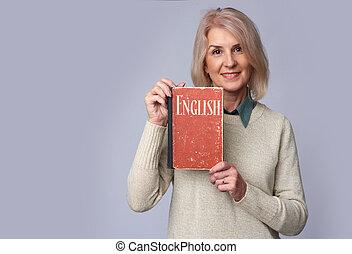 old female teacher holding an English textbook