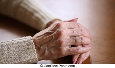 Old female wrinkled hands folded on table close up view -...