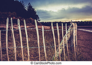 Old fence on the beach at sunset
