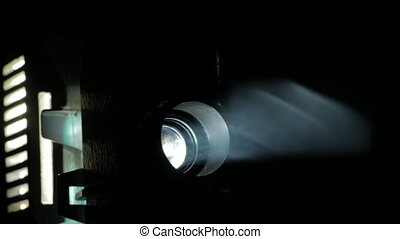 Mechanism of film projector, Front view of an old-fashioned antique Super 8mm film projector, projecting a beam of light in a dark room next to a stack of unraveled film reels. Film projector close up, projector lens and light