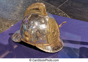 Old fire helmet protects the head of a fire extinguisher
