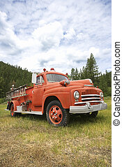 Old fire truck. - Low angle view of old fire truck in field.