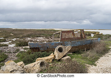 Old fishing boat abandoned on the riverbank