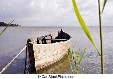 Old fishing boat floating on sea water