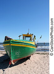Old fishing boat on the beach with blue sky