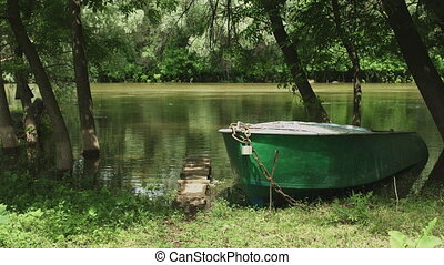 Old fishing boat on the shore of calm river