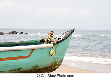 Old fishing boat standing on the sandy beach. India, Goa.