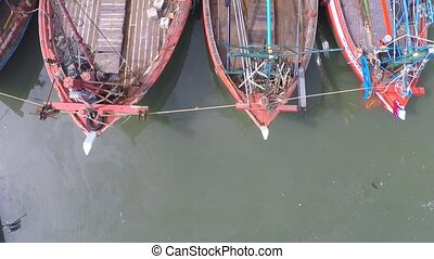 Old fishing boats in green water, view from above