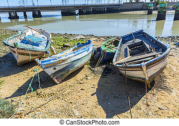 Old fishing boats on the shore of a river