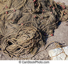 Old fishing nets. Old rope twisted and tied in a bundle on a rough wooden background