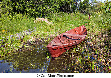 Old fishing wooden boat at the bank of lake in summer day