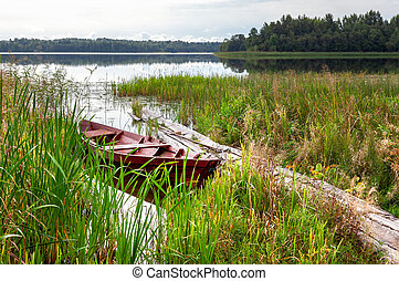 Old fishing wooden boat at the lake