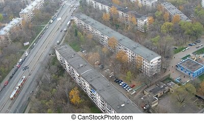 Old five-floor houses stand near to highway on which cars rush