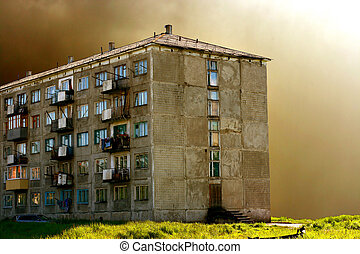 old five story block of flats against clouds background
