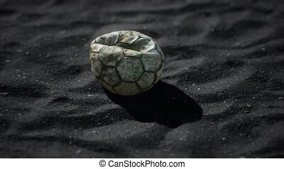 old football ball on the black sand