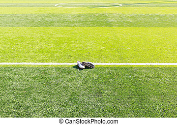 Old football shoes on green grass