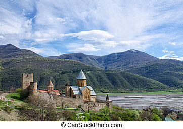 Old fortress on the shore against the backdrop of the mountains, a beautiful spring sky, Ananuri