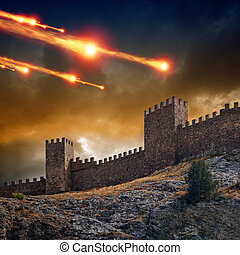 Dramatic background - old fortress, tower under attack. Dark stormy sky, asteroid, meteorite impact