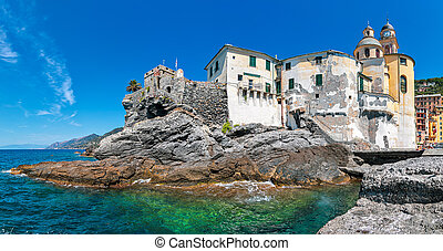 Panorama of medieval fortification and basilica on the rocks in Mediterranean sea under blue sky in small town of Camogli, Liguria, Italy.