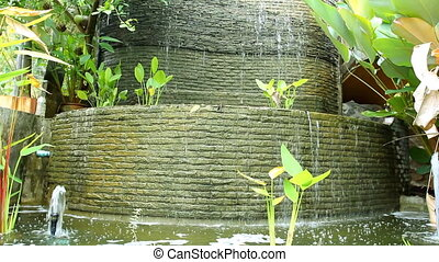 Old fountain in the jungle covered with plants