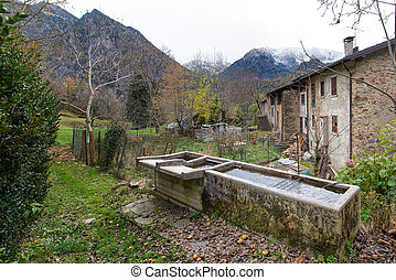 Old fountains in a village of the Italian alps