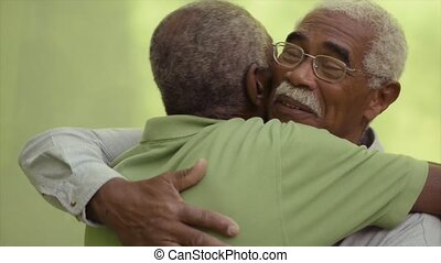 Active retired old men and leisure, two senior black brothers talking and hugging in park. Sequence
