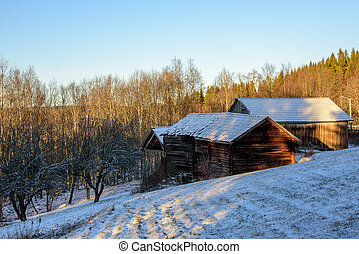 Old frosty barns in a slope