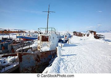 Old frozen ships in the port of Olkhon island on siberian lake Baikal at winter time