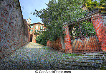 Old gate and narrow paved street in Saluzzo, Italy.