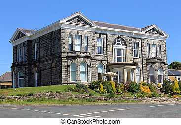 Old Georgian mansion with garden and blue sky background in summer.