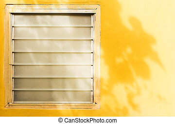 Old glass louver on the yellow wall.