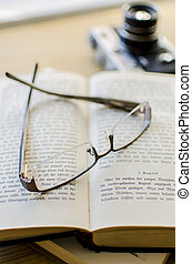 Old glasses, book and camera