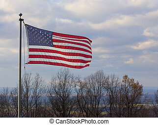 Old Glory - American flag waving from a ridge that overlooks...