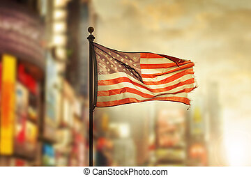 Old Glory in the city - Tattered American flag blowing in...