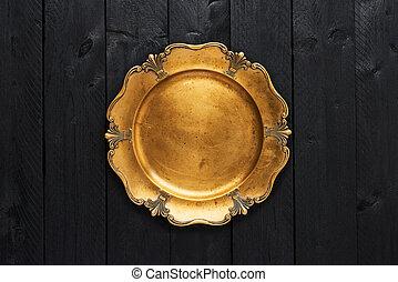 Old golden serving plate on black wooden table