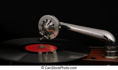 Old gramophone on a dark background. Retro turntable rotates with needle on disc. Music concept. Close up. Slow motion