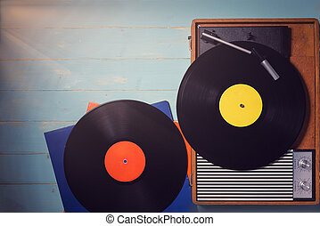 Old gramophone with a vinyl record on rustic wooden table