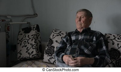 Old grandfather looking thoughtfully aside sits on the couch...