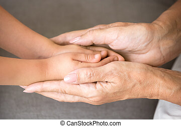 Old grandmother holding hands of little granddaughter, close up