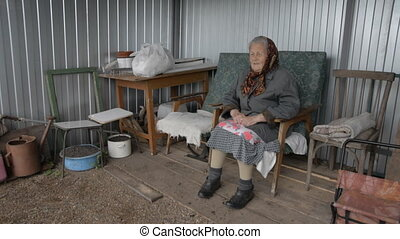 Old grandmother sitting in an armchair outdoors smiling. A...