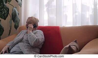 Old grandmother talking on phone sitiing on sofa