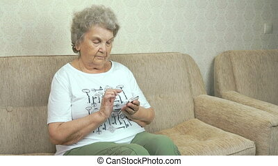 Old granny holding a mobile phone at home - Old granny...