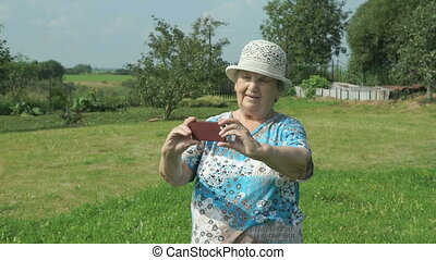 Old granny takes photos the nature of park using a mobile...