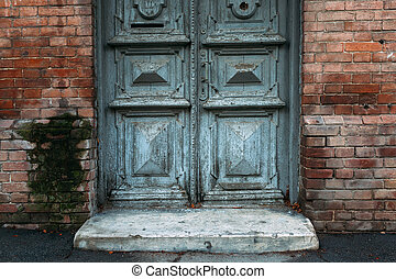 Old gray door with patterns. Brick wall.